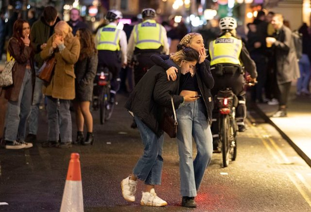 Two friends hug as police ride bikes along a street in Soho in the final night before the capital is plunged into tighter restrictions