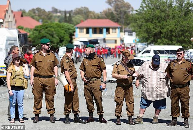 Whites in military uniforms separated from black protesters with razor wire as small town braces for racial violence after latest farm murder in South Africa