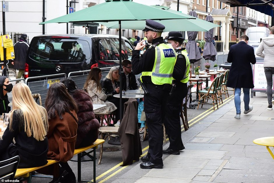 Officers monitor drinkers ahead of the final night before London is plunged into a Tier Two lockdown. Revelers donned coats as they sat outside pubs in Soho earlier in the evening