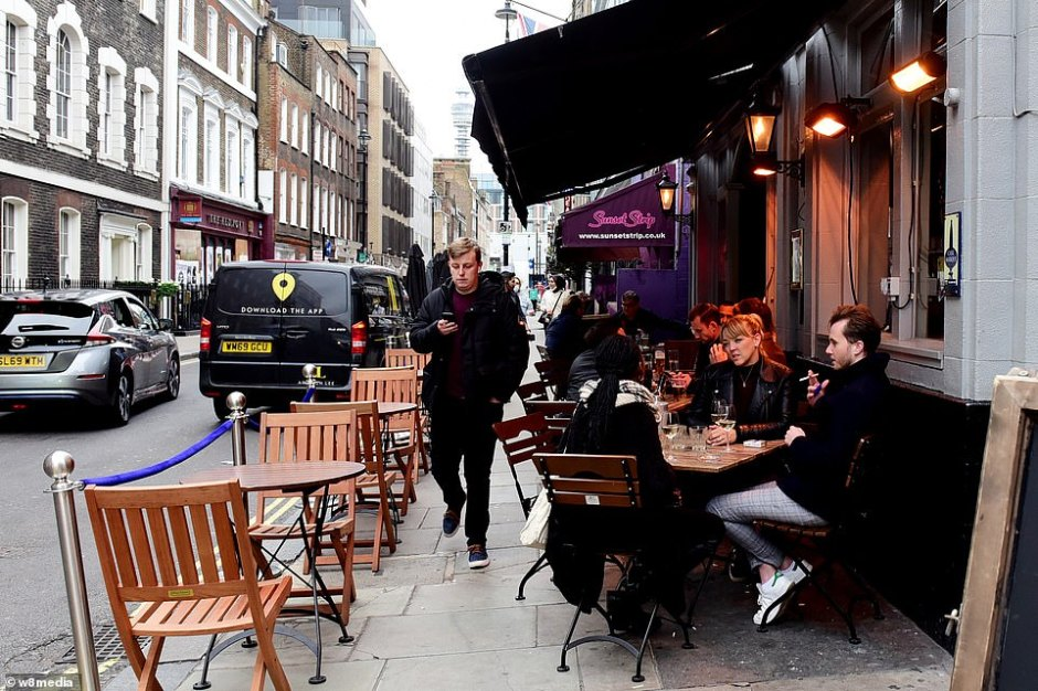 Health Secretary Matt Hancock and Khan yesterday confirmed a ban on people meeting in indoor spaces will begin at midnight tonight in the city. Pictured, people enjoying an evening out in Soho