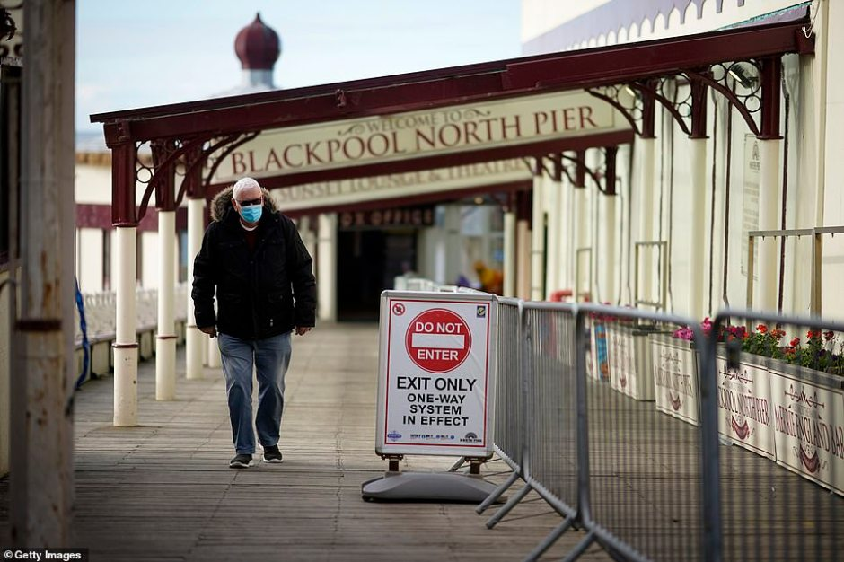 A man wears a face mask against Covid-19 on the promenade in Blackpool, England. The Lancashire region will go into Tier 3 of Covid-19 lockdown restrictions from midnight