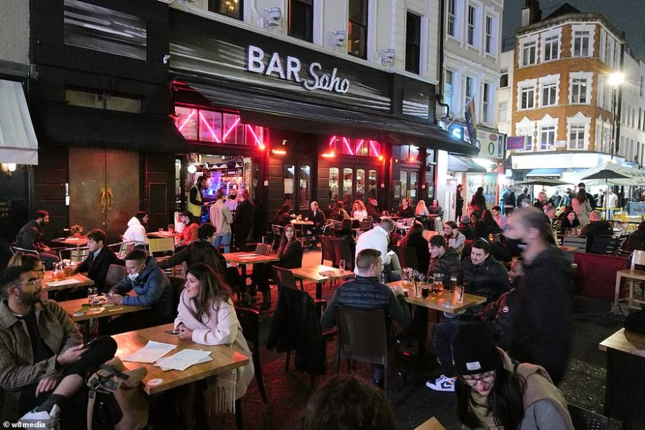 Revellers wore coats and jackets to keep warm as they enjoyed drinks outside Bar Soho in the centre of the capital tonight