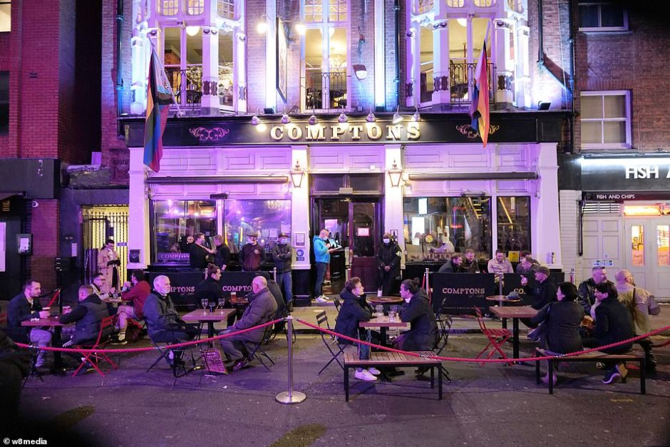 People sit outside Comptons pub in Soho as they enjoy drinks with friends before the level of restrictions increase in the capital at midnight