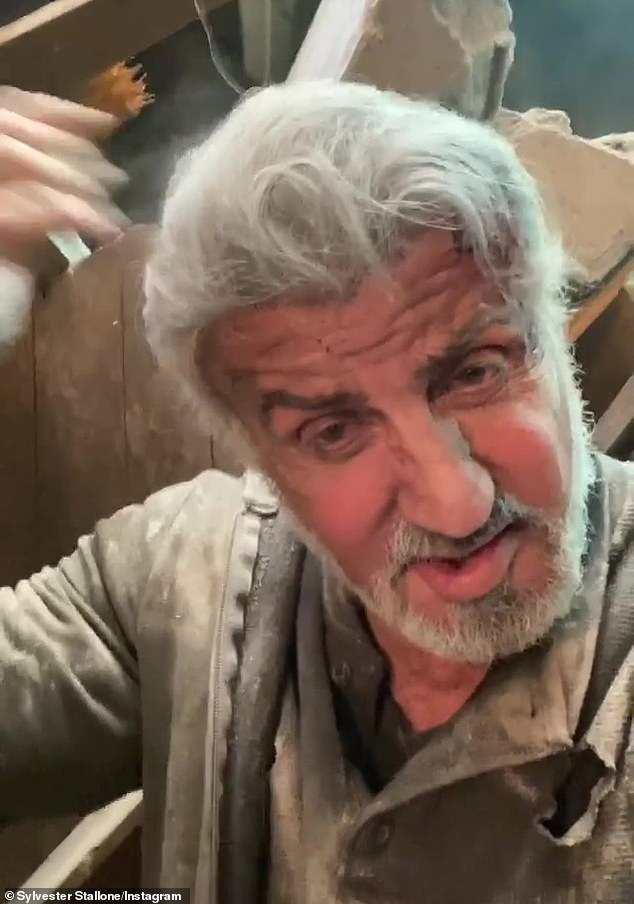 In the thick of it:The Rambo star appeared atop a pile of rubble and broken wood, covered in dust and dirt with a (fake) bloody brow, to announce that he's still doing his own stunts