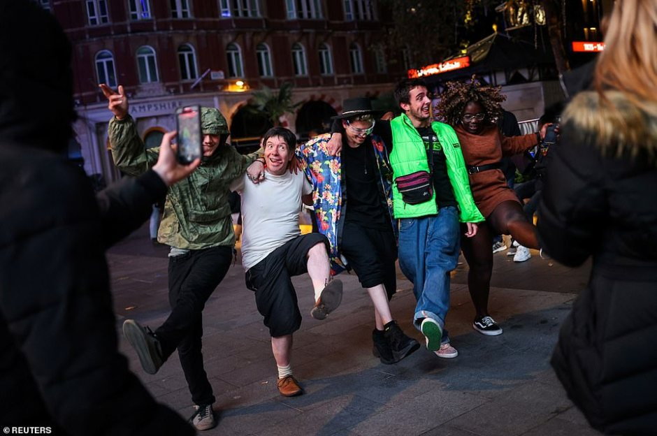 Social distancing measures were completely ignored by these revellers who danced in the street in Soho on Friday