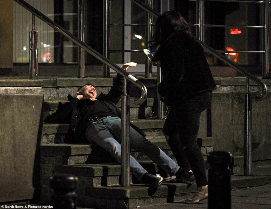 A man falls to the ground on a set of stairs during a night out in Newcastle on Friday night. Instead of helping, his friend appears to be filming him on her phone