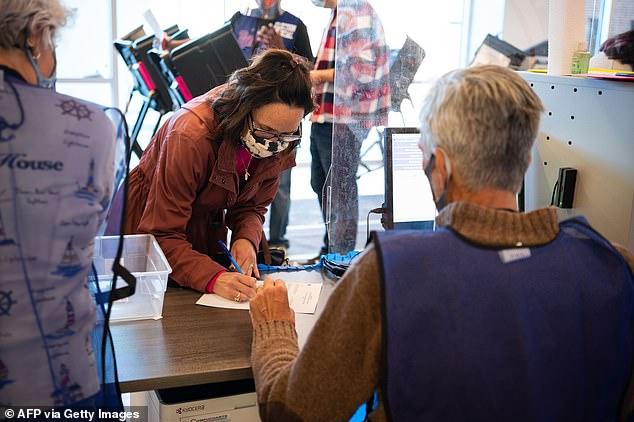 More than 22 million Americans have already cast ballots in the 2020 election. Election official Scott Hagara (R) checks in a voter at the board of elections headquarters during early voting on October 16, 2020 in Painesville, Ohio