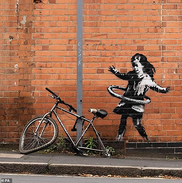 Street artist Banksy has confirmed that he is the artist behind a black and white, the tongue-in-cheek image of a girl hula hooping with a bike tyre, which sits just behind a battered bike chained to a lamp post with an infinity lock