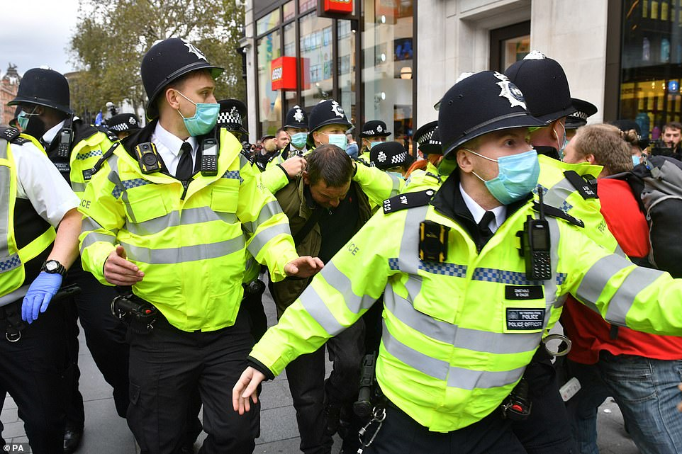 Police officers wearing face masks detained one man during the anti-lockdown rally as it reached Leicester Square, London, earlier today