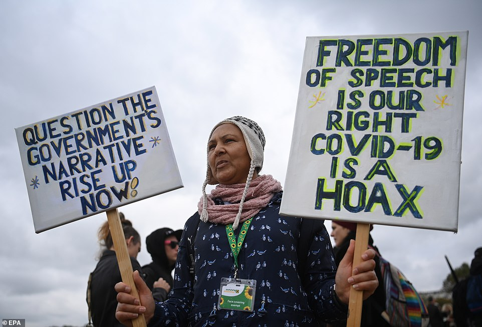 Protesters attended the rally against vaccinations and coronavirus restrictions at Hyde Park as one woman held signs that read: 'Question The Government's Narrative Rise Up Now' and 'Freedom Of Speech Is Our Right Covid-19 Is A Hoax'