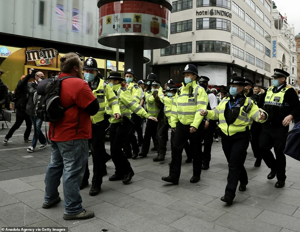It comes as Britain recorded its highest number of coronavirus deaths for more than four months after another 150 victims were announced. Pictured: Police in Leicester Square, London amid the protest today