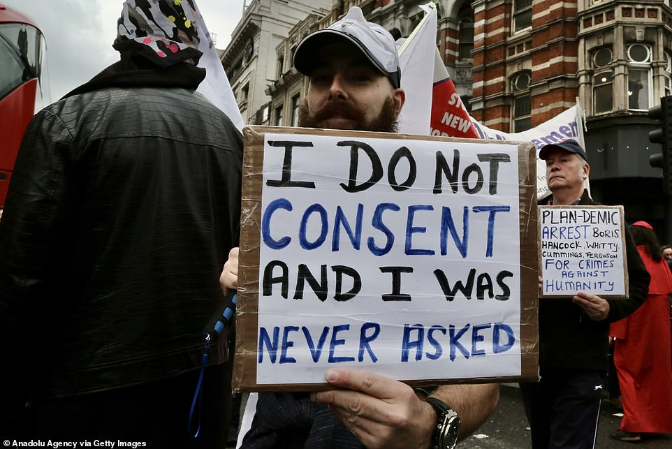 A demonstrator holds a sign reading 'I do not consent and I was never asked' during the rally in London this afternoon
