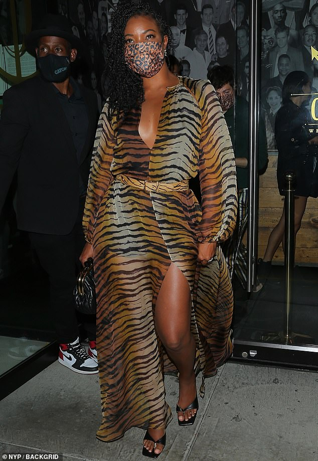 Leg pop: Elevating the floor-length gown, Gabrielle carried a black clutch and wore a pair of kitten heels, as she flashed her toned legs while leaving her dinner with friends