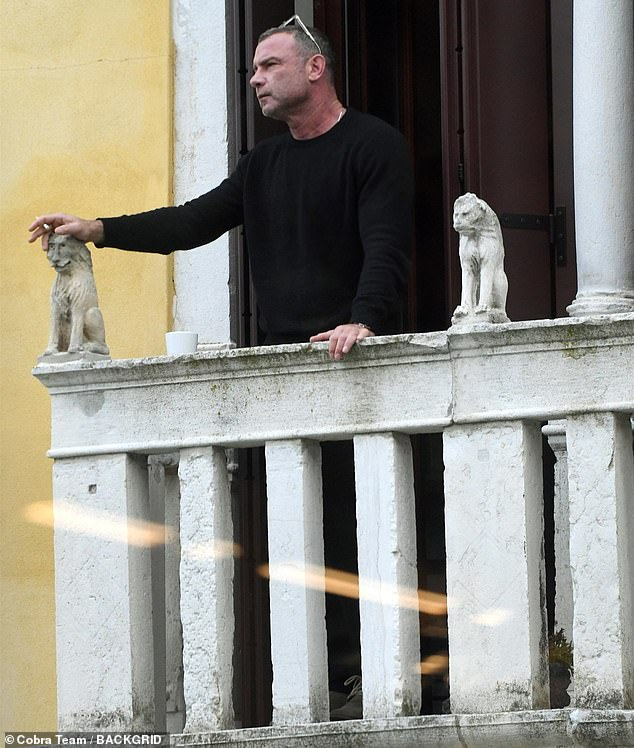 Taking in the sights: Liev Schreiber, 53, relaxed with a cigarette and coffee on his balcony in Venice on Saturday while wearing a sleek black sweater