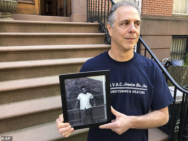 Daniel Arbeeny, 57, is helping organize a mock funeral for Governor Andrew Cuomo's 'leadership and integrity' on Sunday in front of a Brooklyn nursing home where his father was a patient before he died of COVID-19 earlier this year. Arbeeny is seen above in Cobble Hill, Brooklyn, holding up a photo of his late father, Norman