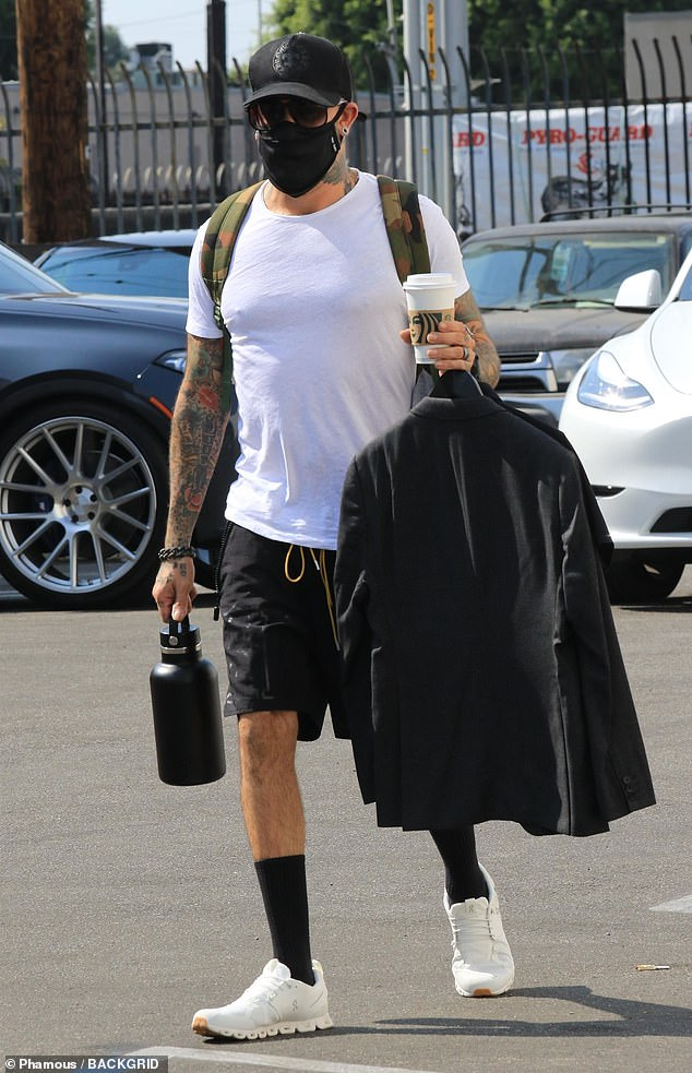 Fit: Despite covering the majority of his face under a CDC-recommended face mask, McLean showed off his bulging and tattooed biceps in the parking lot