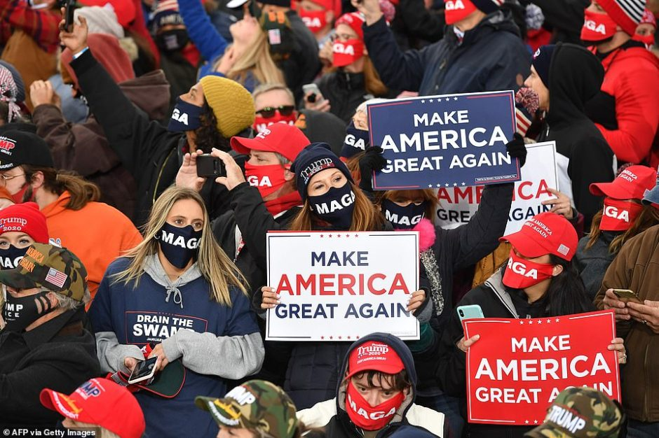 Supporters hold up Make America Great Again banners for Trump at the rally where he boasted he had 'done more in 47 months than Biden has done in 47 years'