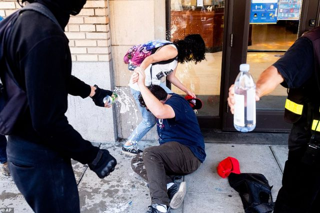 A man in a Trump 2020 t-shirt was seen having a drink poured on him by a counterprotester as he cowered on the ground