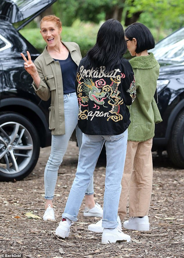 Hey guys!They paired their wide pants with matching white, stacked sneakers and carried notepads, distracted while a cheerful Olivia Vivian mucked about behind them