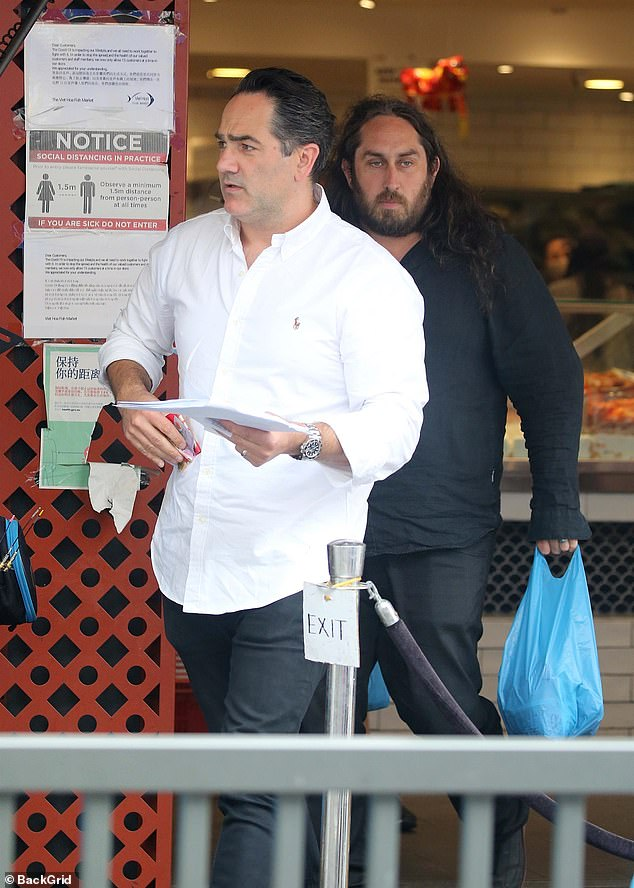 A helping hand:He was accompanied by comedian Ross Noble, who also had plastic bags