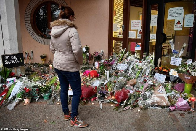 Pictured: A woman views floral tributes outside the school inConflans-Sainte-Honorine today following the death of a French teacher
