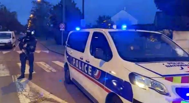 Pictured: Armed police stands near a police car in the outskirts of Paris where the attack took place.The first bloodbath took place in Conflans-Sainte-Honorine, a suburb some 25 miles from the centre of the French capital on Friday