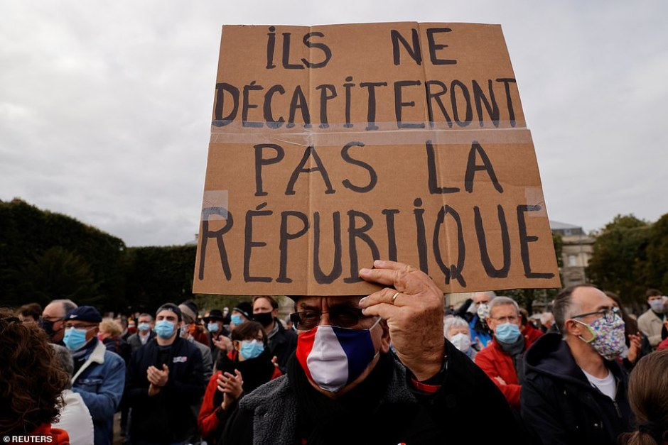 A protester in the French capital holds aloft a placard which reads 'they won't decapitate the Republic' in the wake of the brutal attack