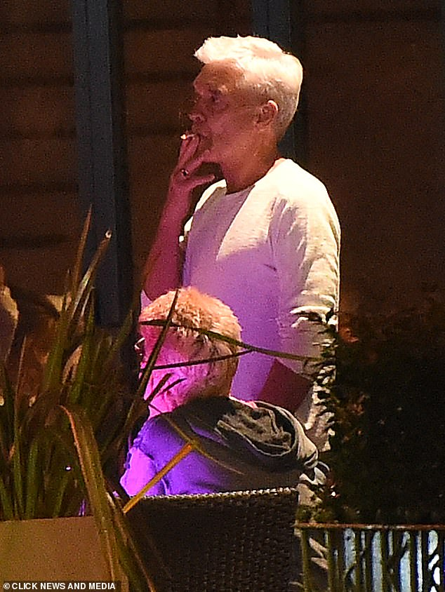 Night out:Phillip Schofield was spotted smoking a cigarette as he enjoyed a fun night out with his friends in Richmond, London, on Tuesday