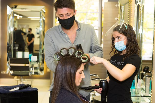 As part of the long process, Claire had several large rollers on the top of her head to create the bouncy wave look while lots of people worked around her to create the ideal style (pictured)