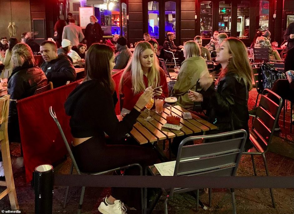 Revellers brave the elements as they  swap a night in at home to sit outside a number of bars and restaurants in the city