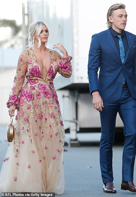 Kjiersten Straub, the partner of the Gold Coast Suns player Hugh Greenwood (right), certainly dressed to impress in a Disney-inspired ball gown covered in pink roses - but the tailoring left a lot to be desired with an ill-fitting waistband hanging too lose around her midriff and excess fabric bunching around her wrists