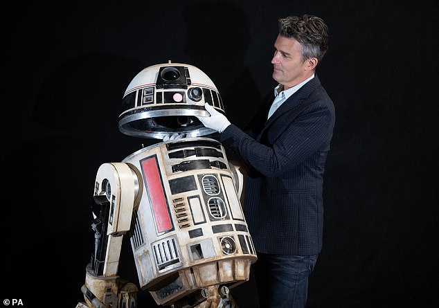 Legendary: The R2-S8 droid from the 2008 Star Wars outing Solo: A Star Wars story is going for £40-60,000. Pictured with Prop Store founder and CEOStephen Lane