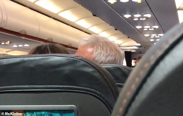 The man, above, tells his wife: 'Shut up you f**ing imbecile' before she is heard slapping him.He then retaliated to the slap, according to the passenger who filmed the video