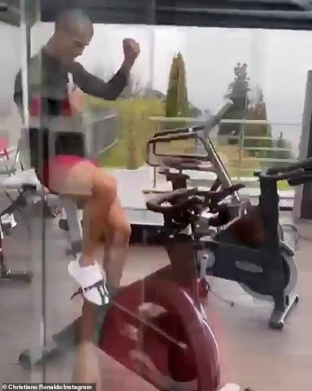 Working out: He then hopped inside to his mordern, glass gym, jumping onto an exercise bike