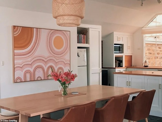 The dining area and kitchen are open plan by design so Chloe and Patrick simply elevated the space with some wooden textures and artwork