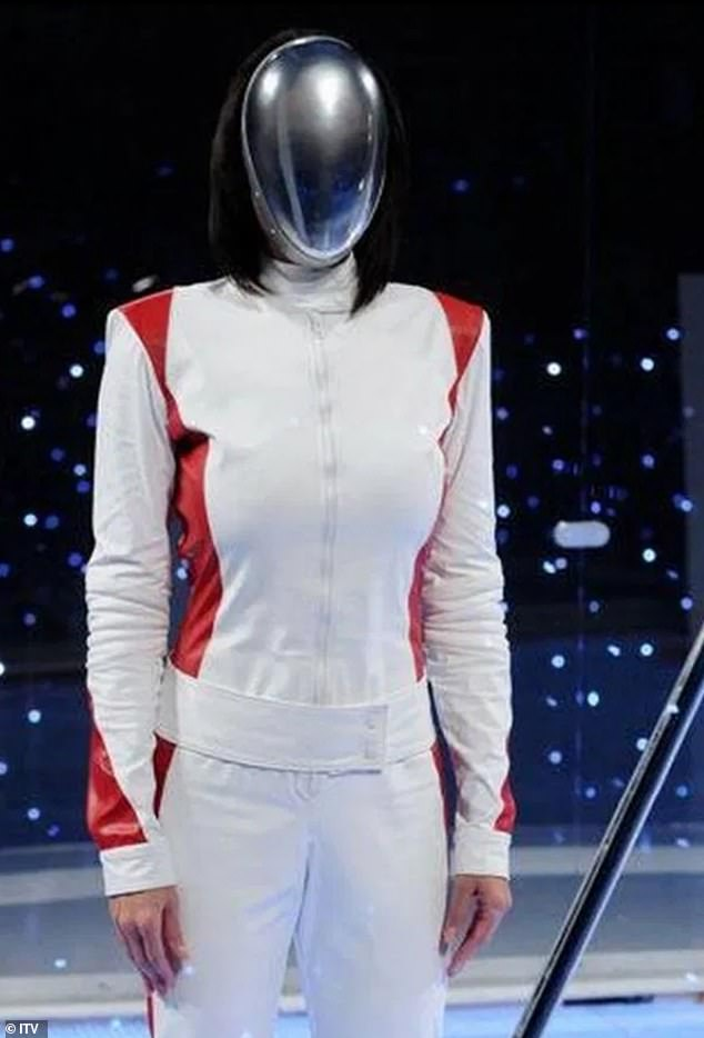 In the character: The model is still seen during The Cube in her white and red costume with her futuristic mask obscuring the identity