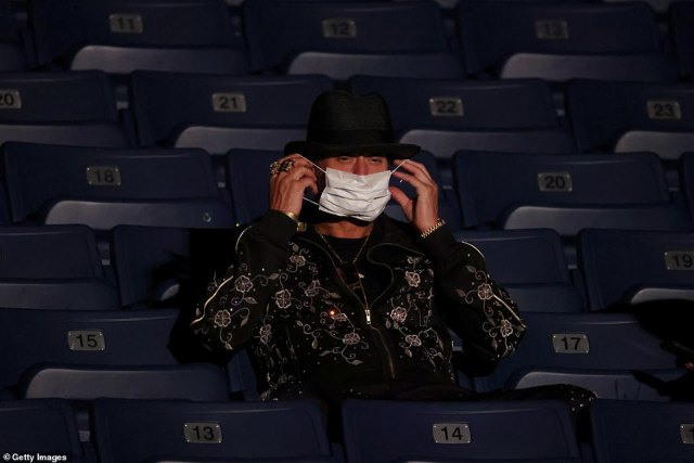Musician Kid Rock, who is an outspoken Trump supporter, puts on a face mask at the final presidential debate