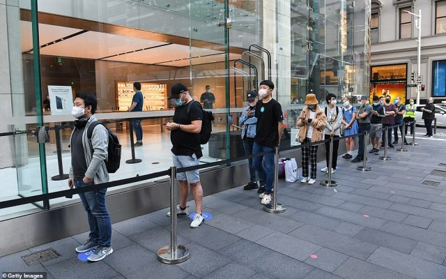 Customers line up outside the Apple Store in George Street with social distancing in operation in order to look at the new iPhone 12 on sale on Friday in Sydney