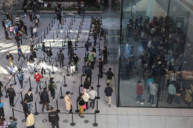 People line up to enter an Apple flagship store as sales begin for the new iPhone 12 and iPhone 12 Pro in Beijing, China on Friday