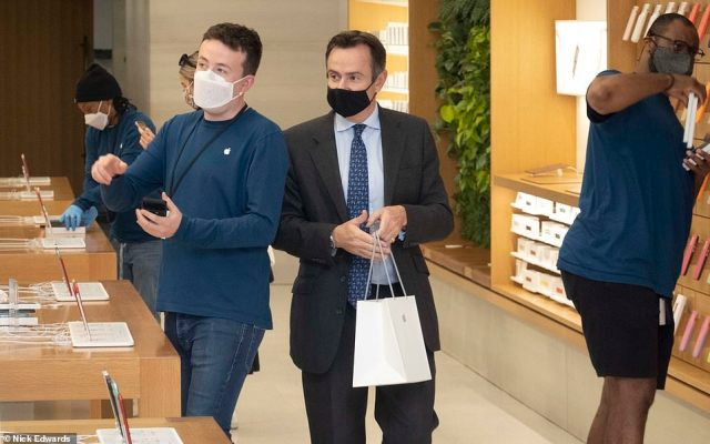 One masked customer having made his purchase at the Apple Store in Regents Street, London next to a masked member of staff