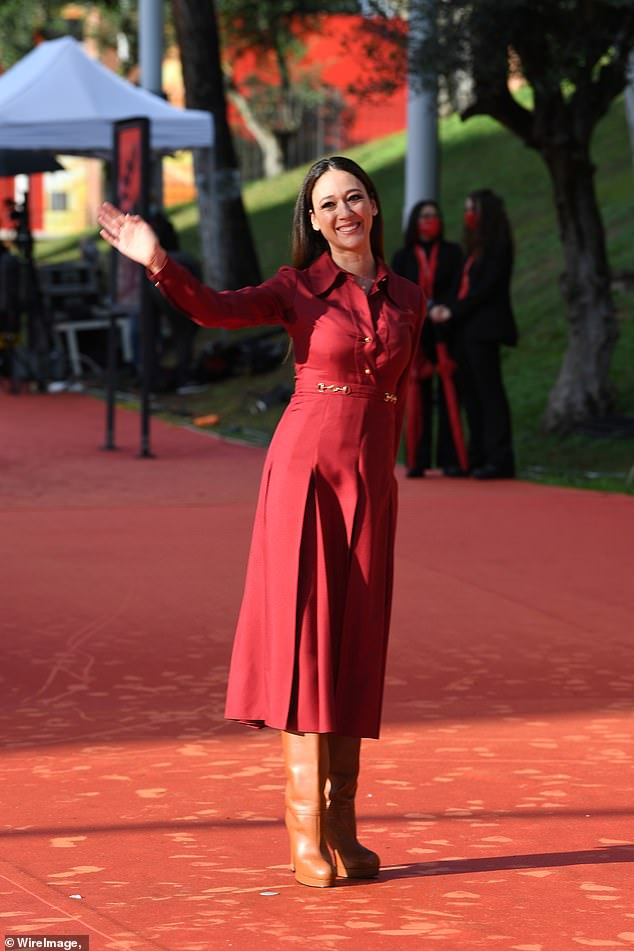 Chic: Dajana was stylish when she slipped into a red long-sleeved dress that had a pleated skirt and a statement belt