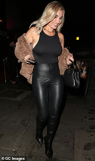 Style: She teamed her top with tights leggings and a brown fur coat as she left the room in a good mood