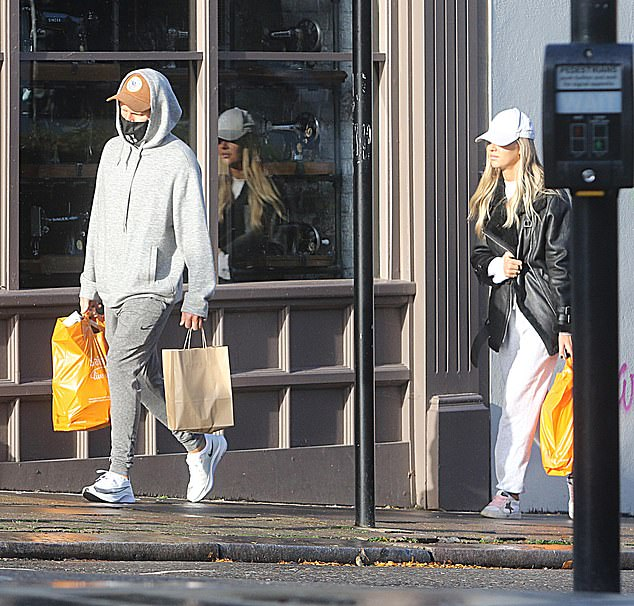 Low-key: Jamie wore gray sweatshirts with a baseball cap and face mask
