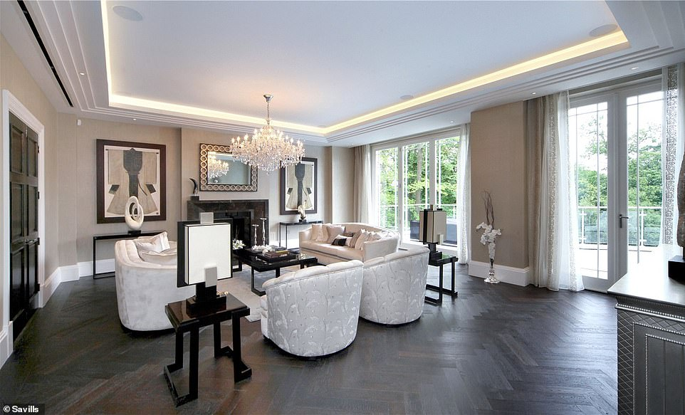 The main living room has seating surrounding a feature fireplace and bi-folding doors onto the garden