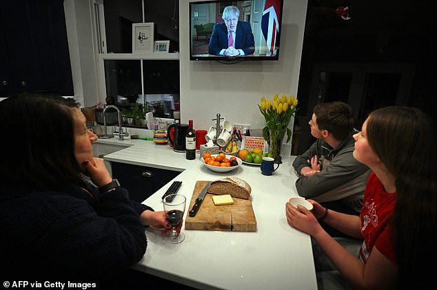He will tell Cambridge Law School that the use of coercion to try to quell the pandemic is unprecedented in British history, even in times of war, and that it runs counter to fundamental freedoms. A family is seen seated to watch Prime Minister Boris Johnson address the nation in March