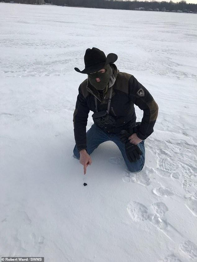 Meteorite hunter Robert Ward with the meteorite on Strawberry Lake near Hamburg, Michigan
