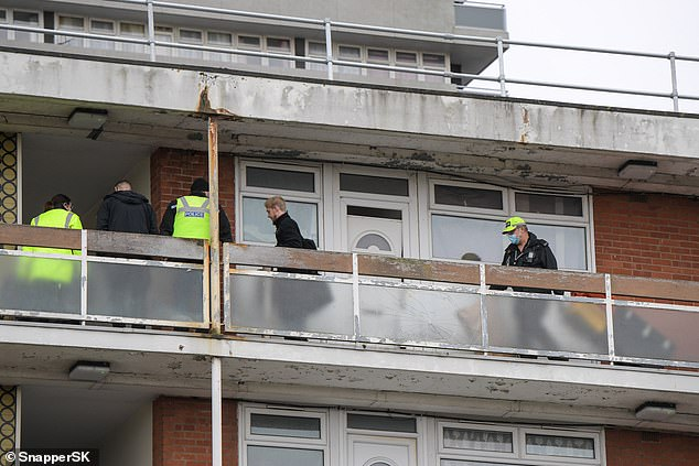 The hunt came after the body of Mrs Williams, 58, was discovered at her flat at Emily Smith House, Riley Square, just before 11pm on Sunday. Pictured: Police at the scene