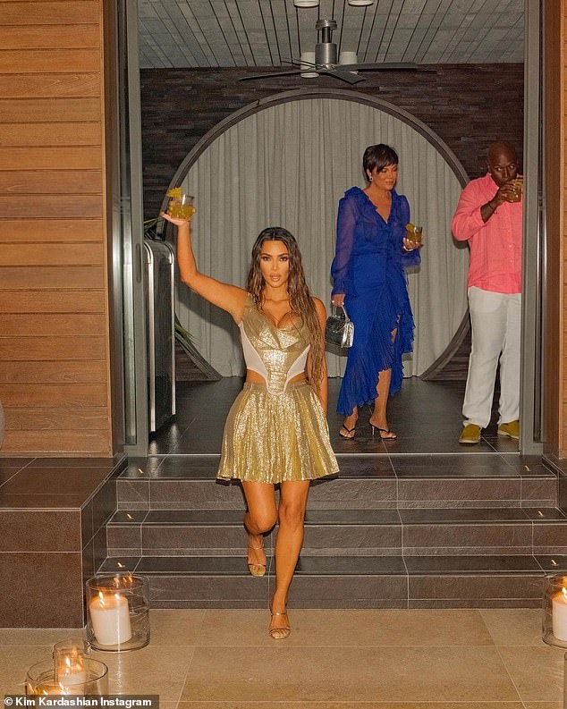 Here's to Kim!  The reality TV star lifted a tropical drink while descending a staircase