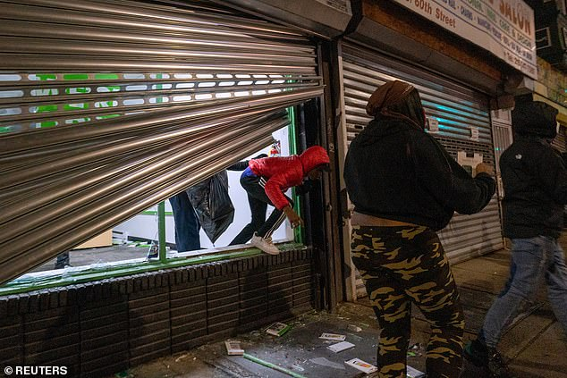 Looters run out of a cellphone store following protests over the police shooting death of Walter Wallace in Philadelphia on Tuesday