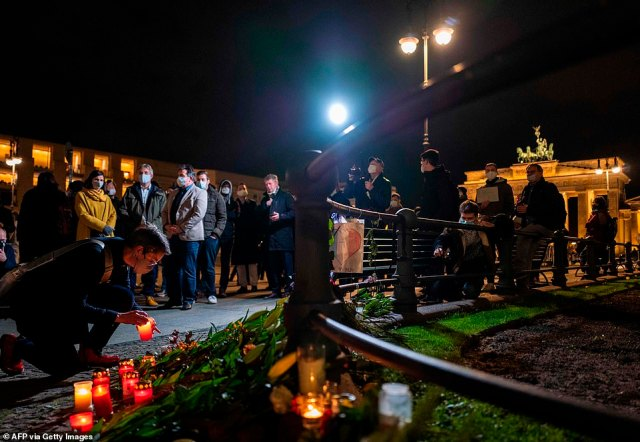 A woman places a candle at a makeshift memorial for the victims of the Nice attack, in front of the French embassy in Berlin